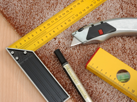 Piece of carpet with measuring square, marker and utility knife