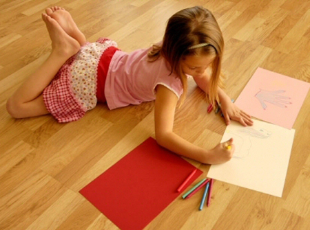 young girl laying on laminate floor while drawing