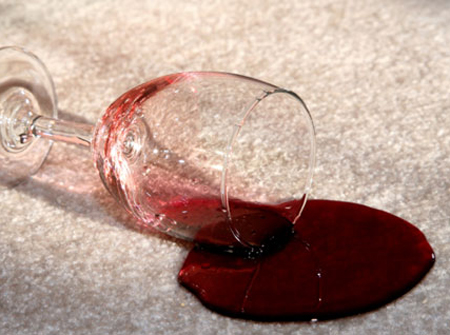 glass of wine knocked over with spilled wine on carpet